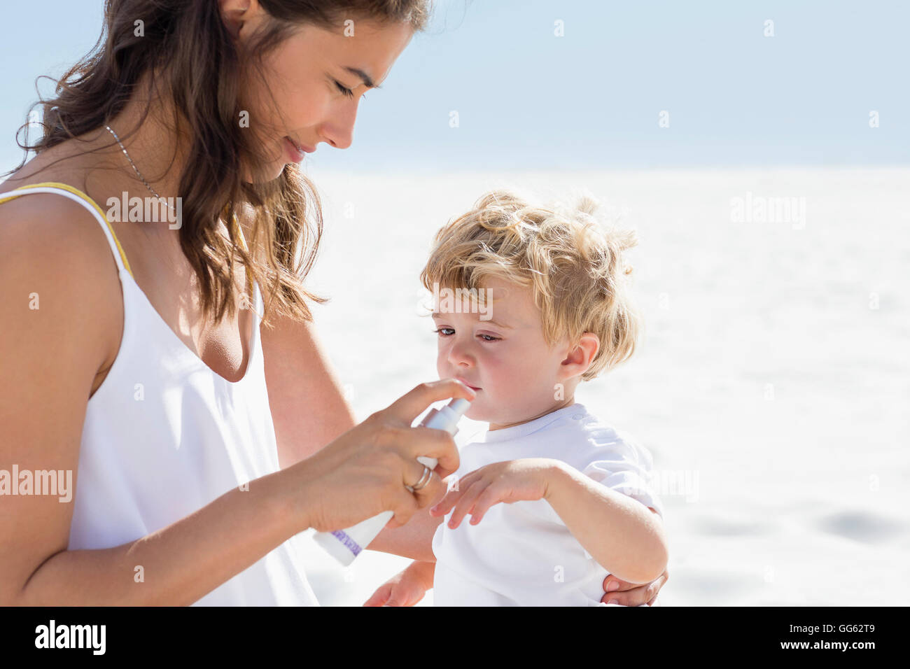 Woman spraying sunscreen on her baby hand - Stock Image