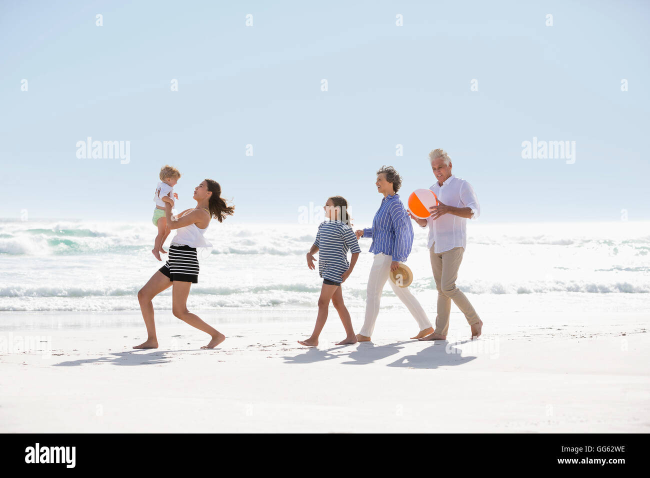 Multi-generation family walking on the beach - Stock Image
