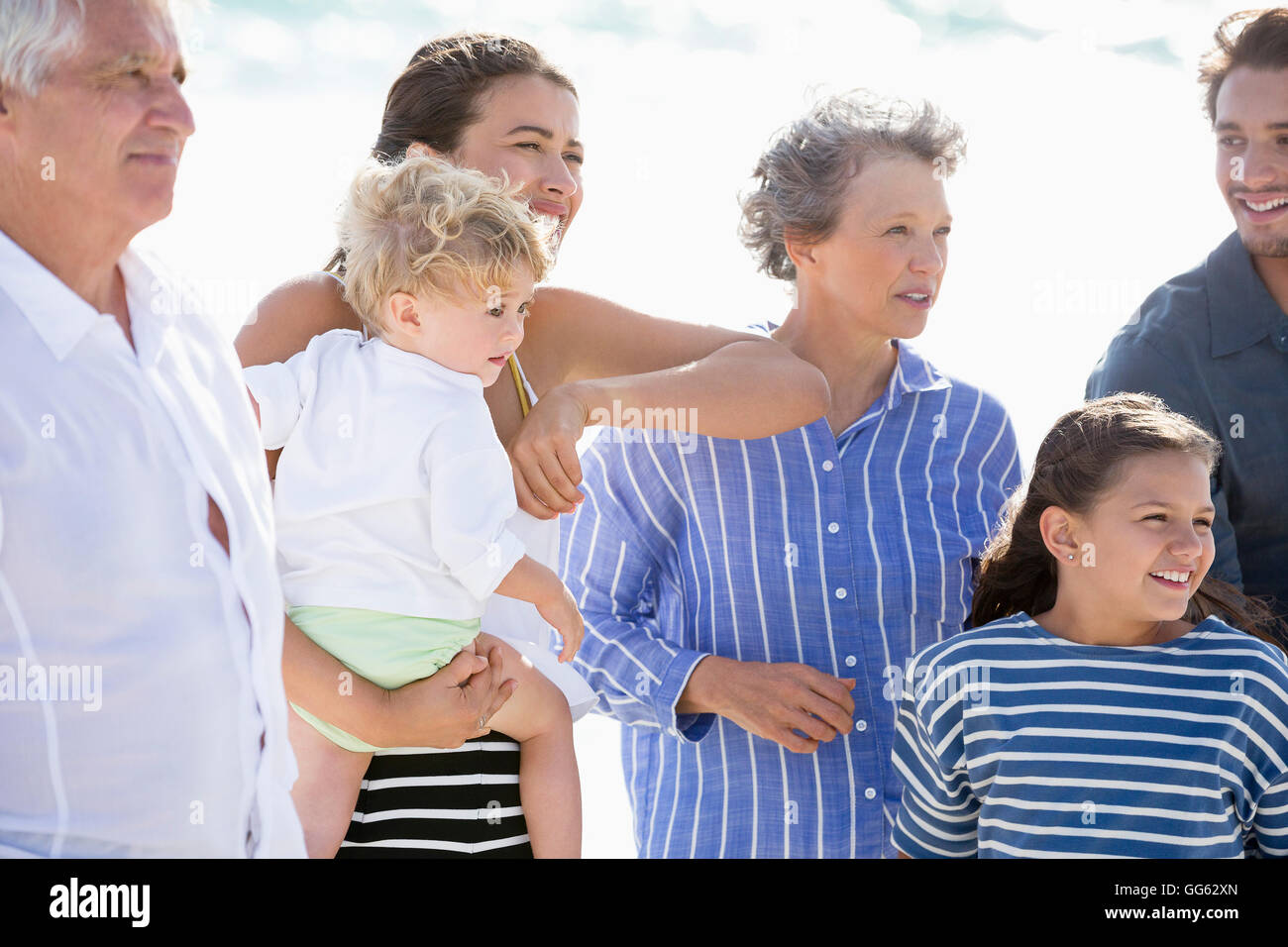 Multi-generation family standing on the beach - Stock Image