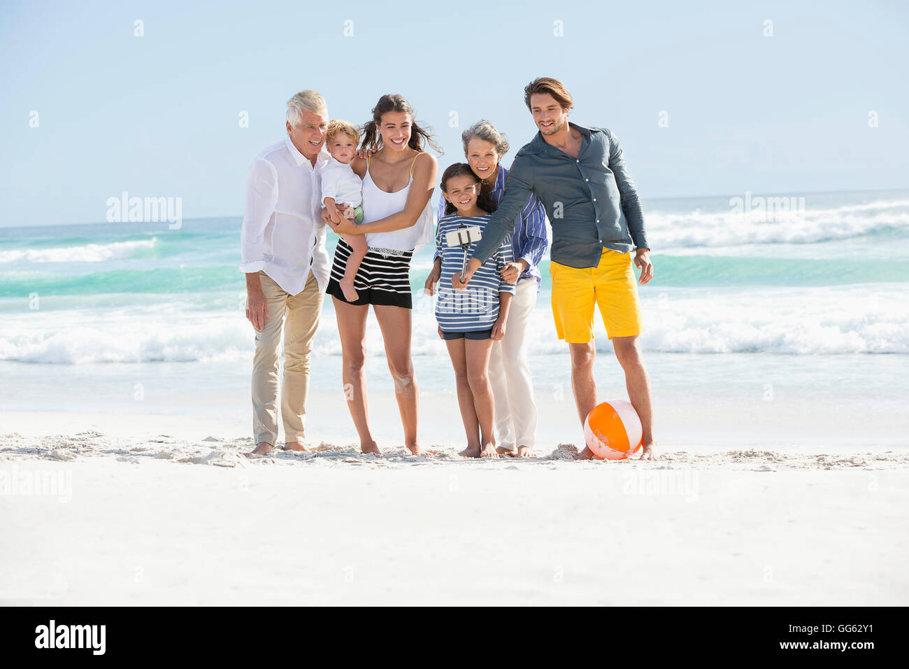 Multi-generation family standing on the beach taking selfie - Stock Image