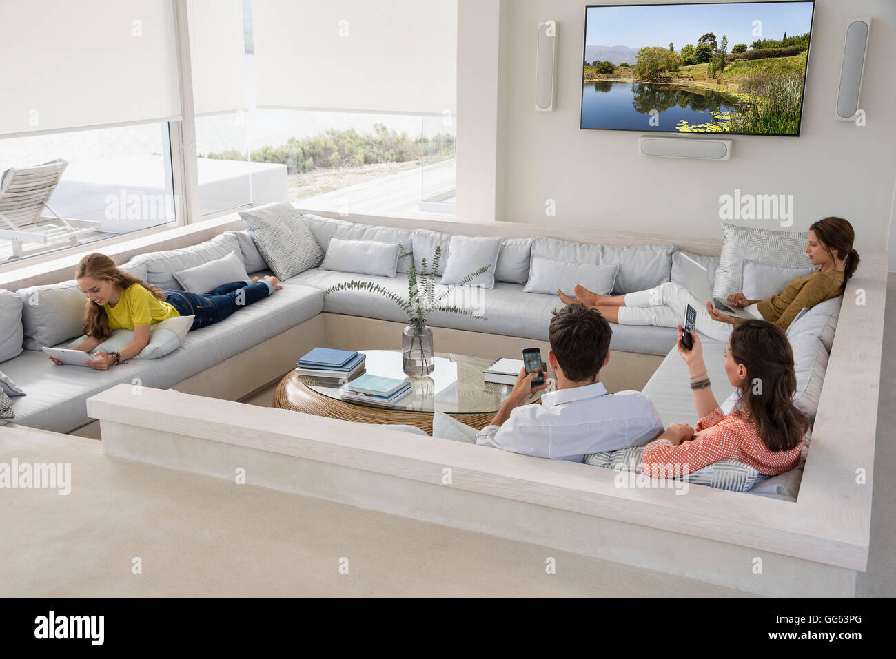 Family in living room busy in different activities Stock Photo ...