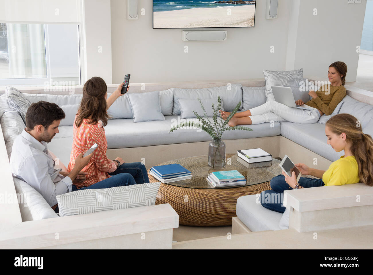 Family in living room busy in different activities Stock ...
