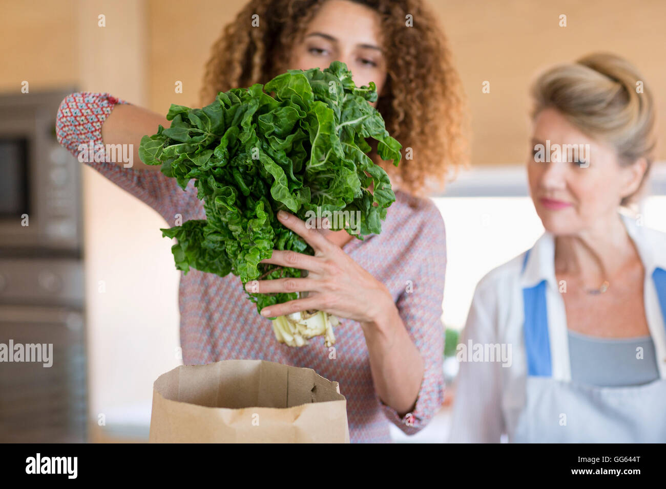 Senior woman with daughter in kitchen - Stock Image