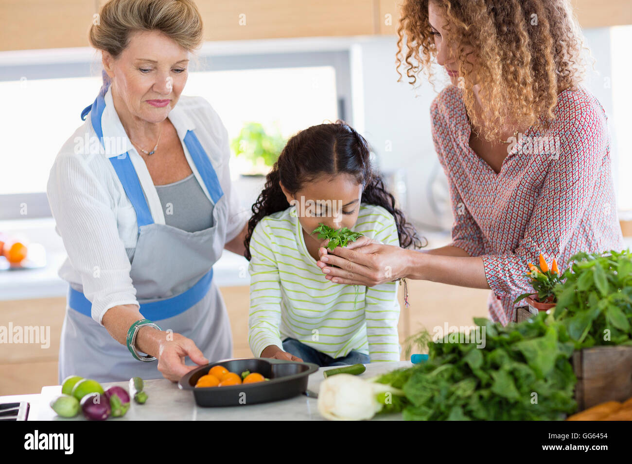 Senior woman with daughter and granddaughter in kitchen - Stock Image