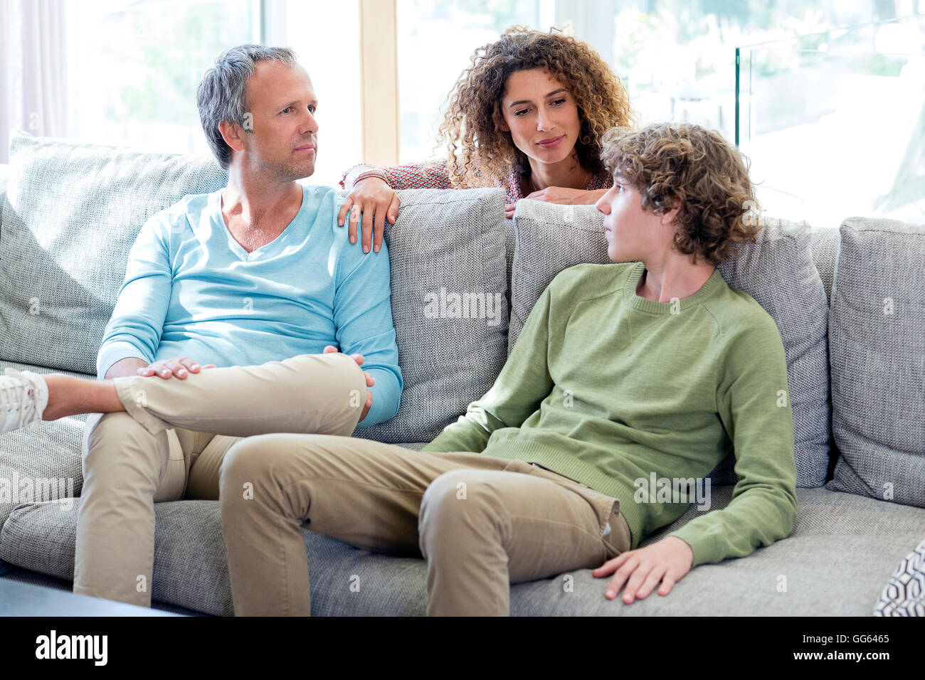 Family having a discussion in living room at home - Stock Image