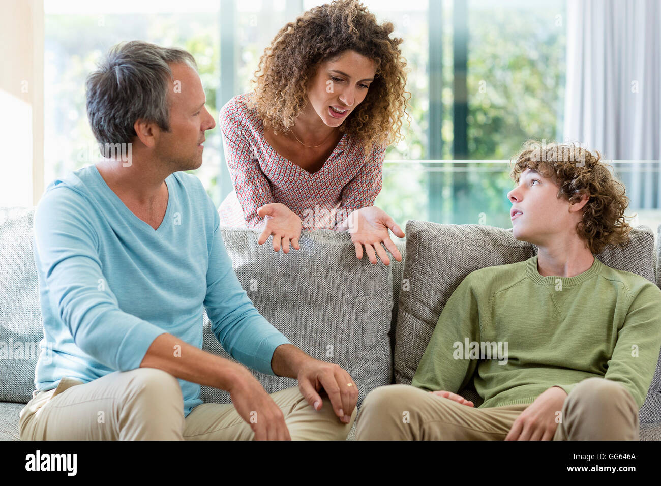 Happy family talking in a living room at home - Stock Image