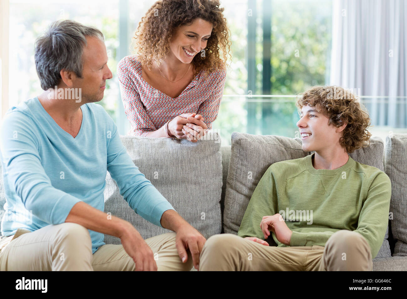Happy family smiling in a living room at home - Stock Image