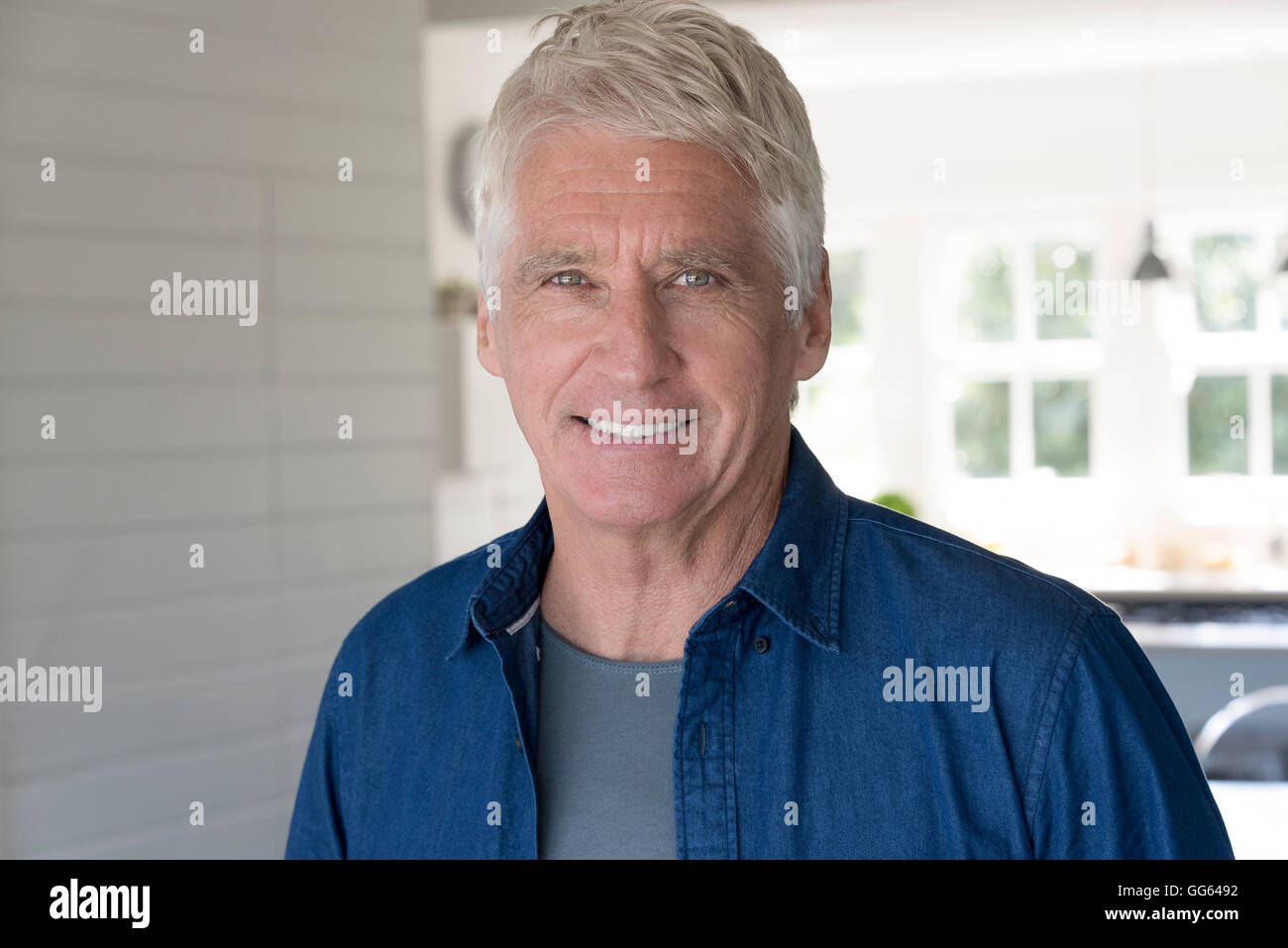 Portrait of happy senior man smiling at home - Stock Image
