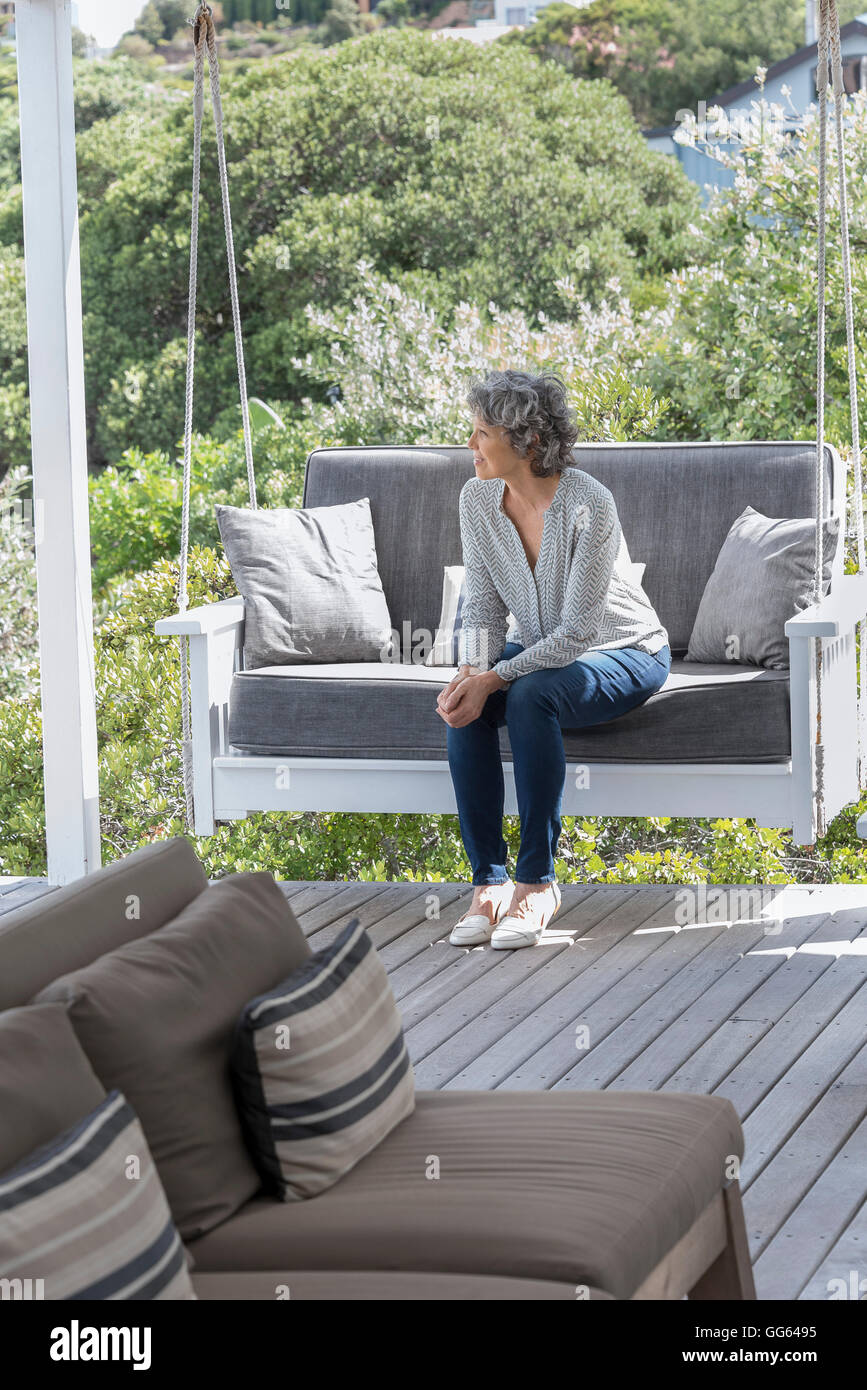 Happy woman relaxing on swing chair at porch - Stock Image