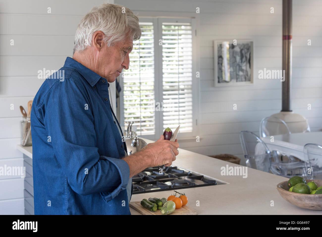 Senior man preparing vegetables in kitchen - Stock Image