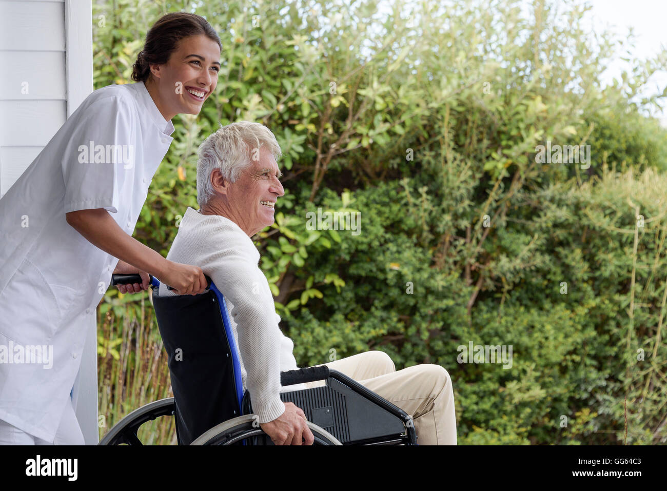 Female nurse assisting senior man in wheelchair on porch - Stock Image