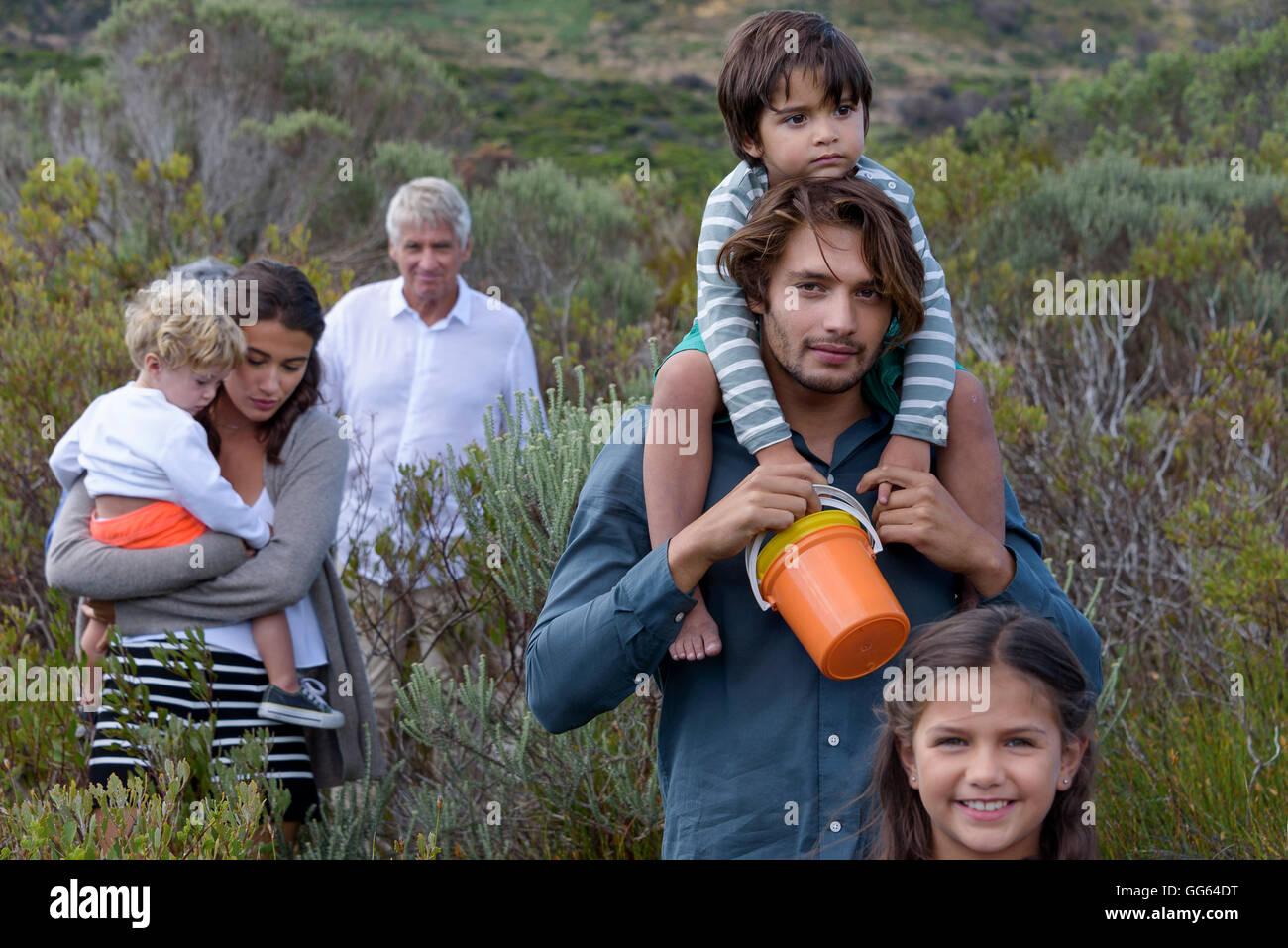 Happy multi-generation family walking on landscape - Stock Image