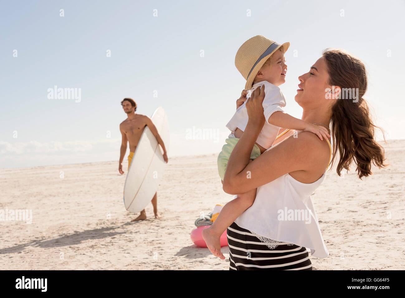 Happy young family enjoying on beach - Stock Image