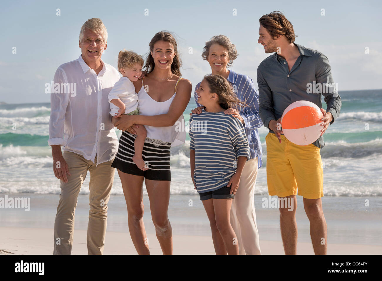 Portrait of happy multi-generation family standing on beach - Stock Image