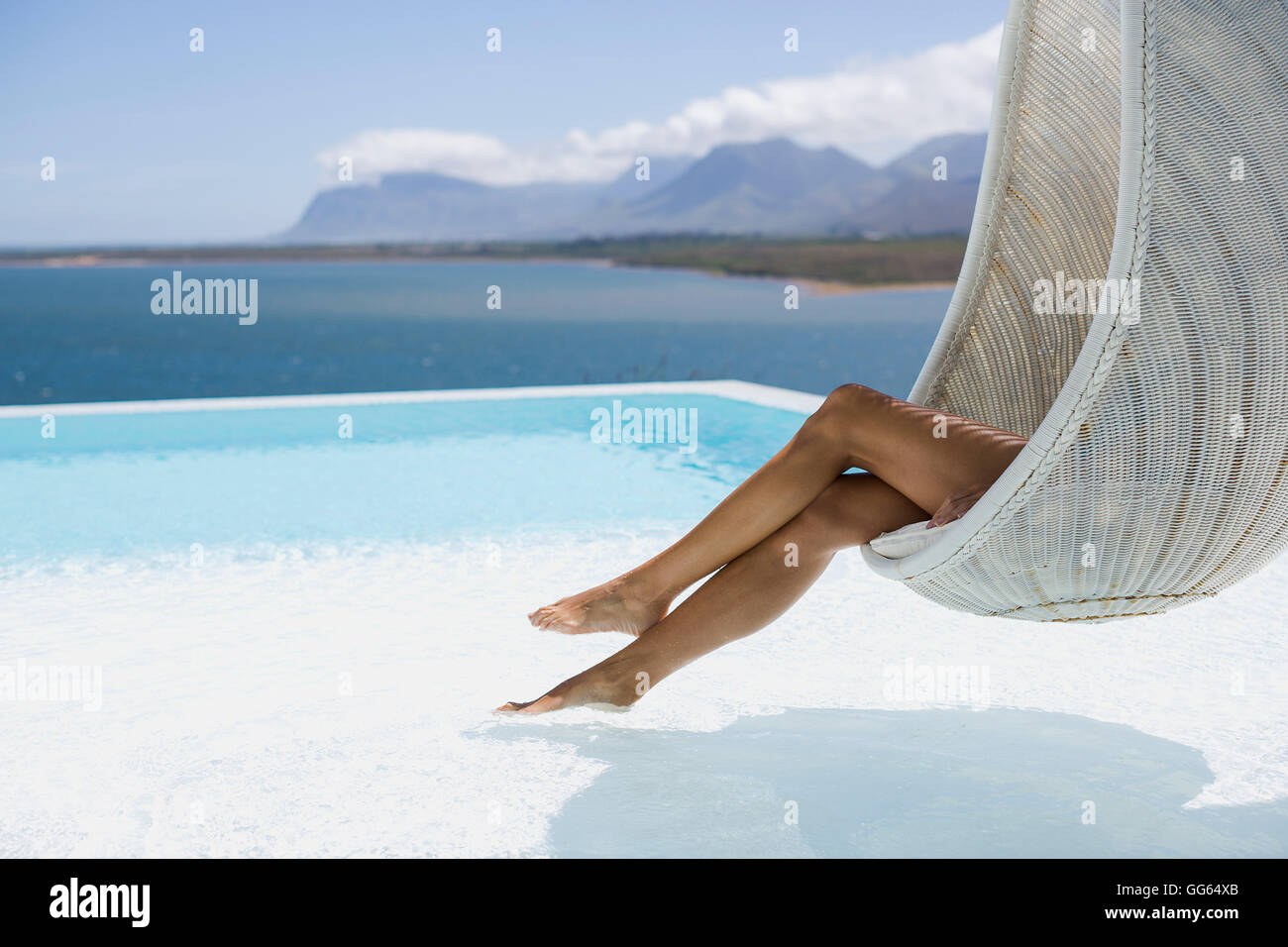 Low section view of a woman relaxing in wicker swing - Stock Image