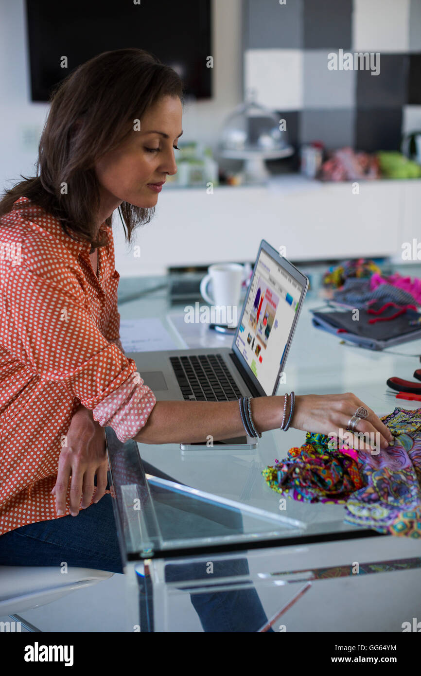 Female fashion designer working in her office - Stock Image