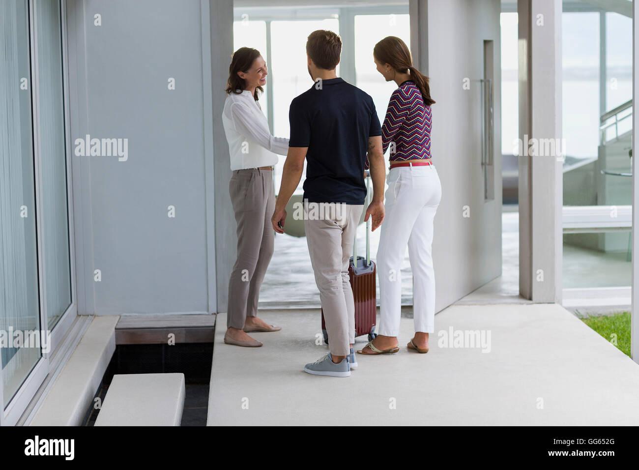 Woman welcoming her friends at doorway - Stock Image