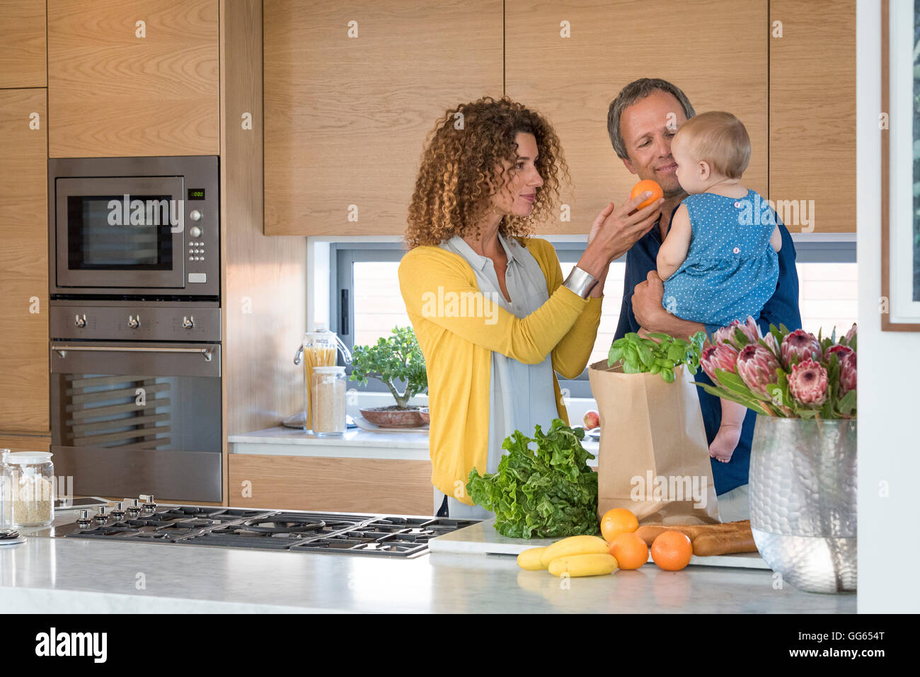 Woman giving orange to her daughter - Stock Image