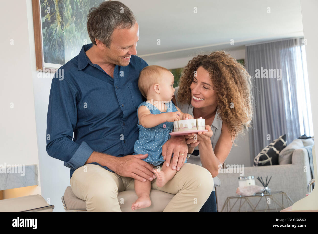 Happy woman giving toy to her baby daughter sitting on her father lap - Stock Image