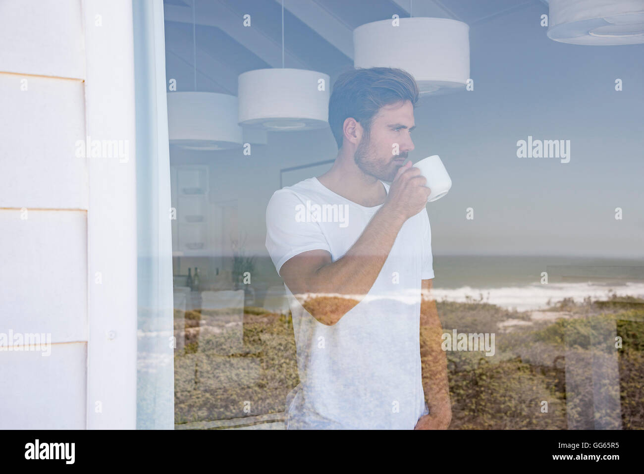 Young man looking through window with cup of coffee - Stock Image