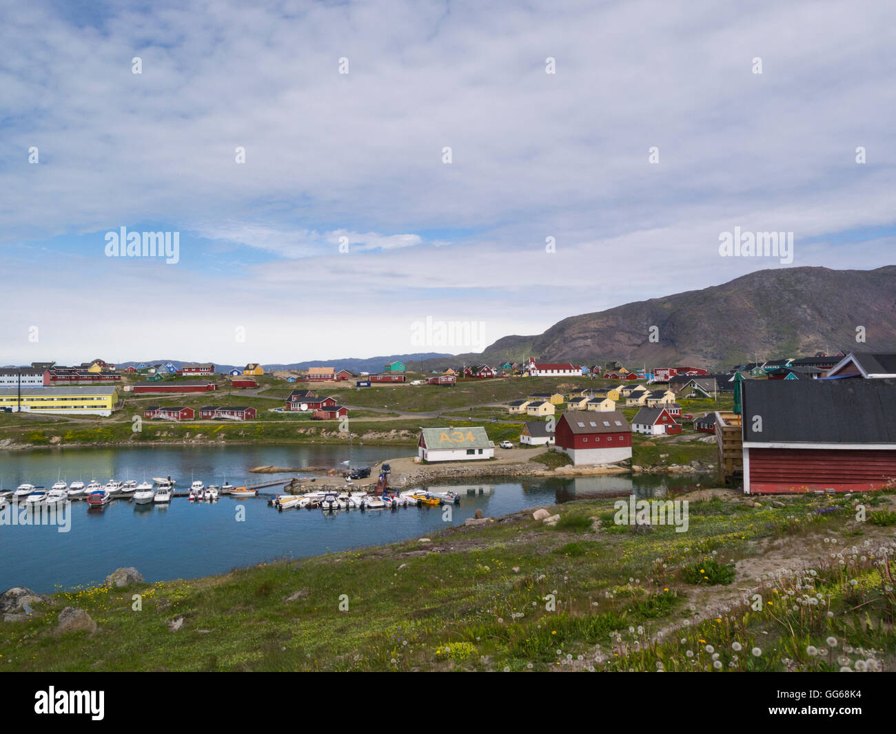 View across Tunulliarfik Fjord headland to Narsaq History Museum buildings with moored fishing boats Southern Greenland Stock Photo