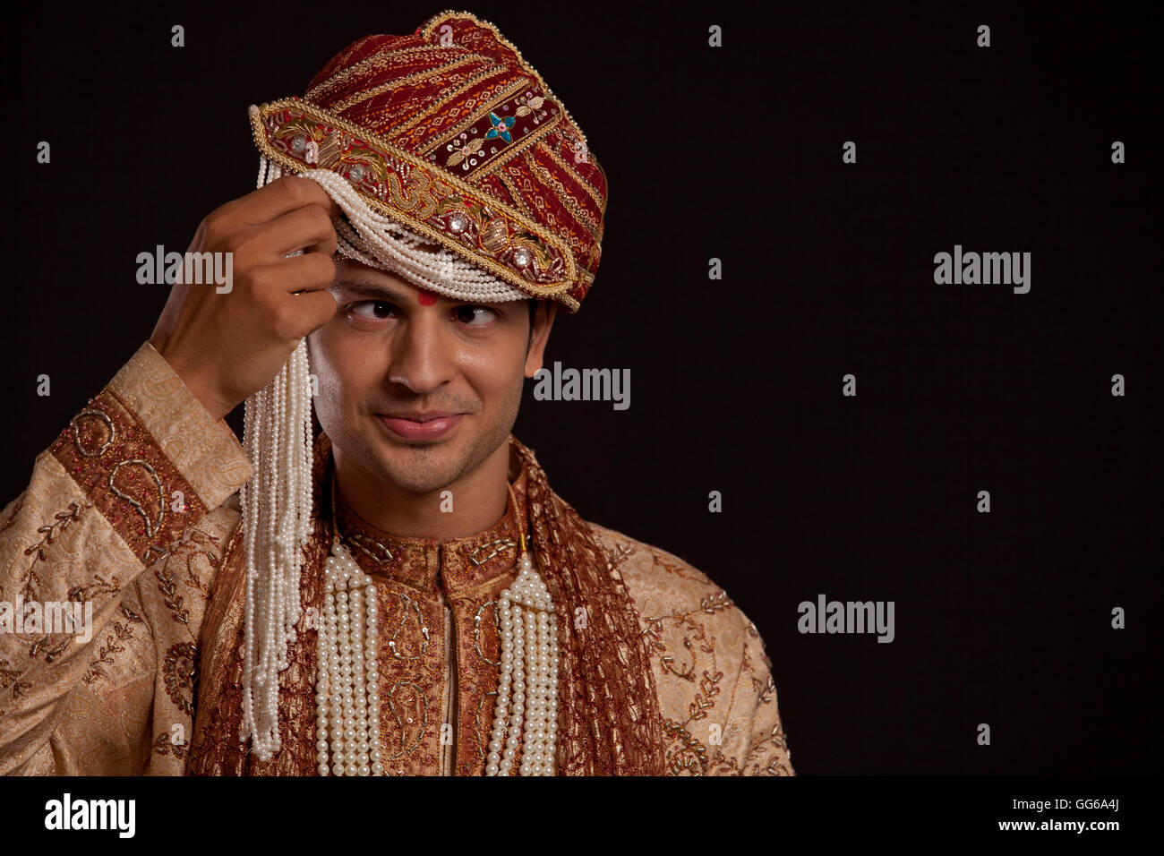 Gujarati groom with a headdress making a face - Stock Image