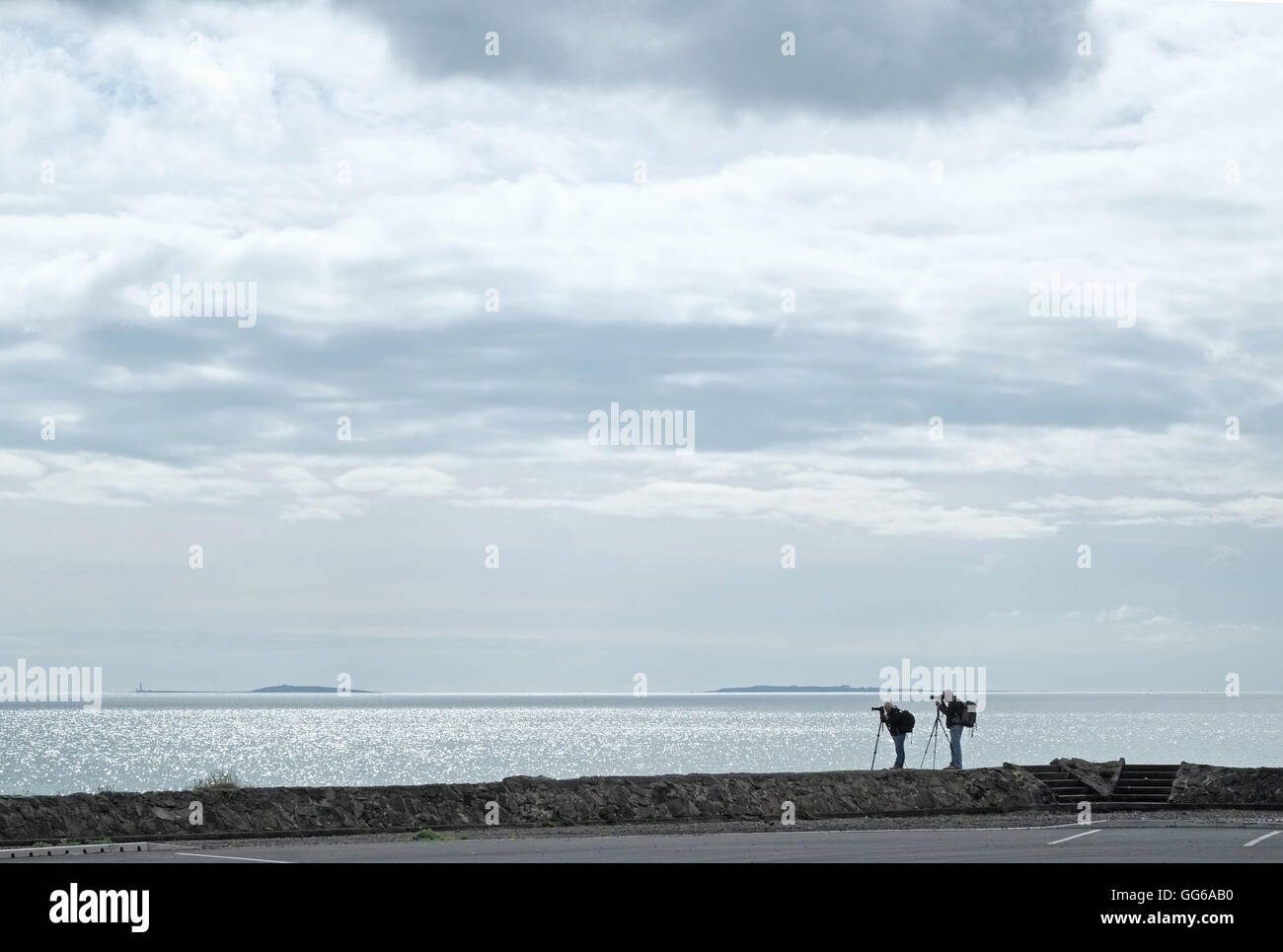 Two photographers with tripods, by Belfast Lough. - Stock Image