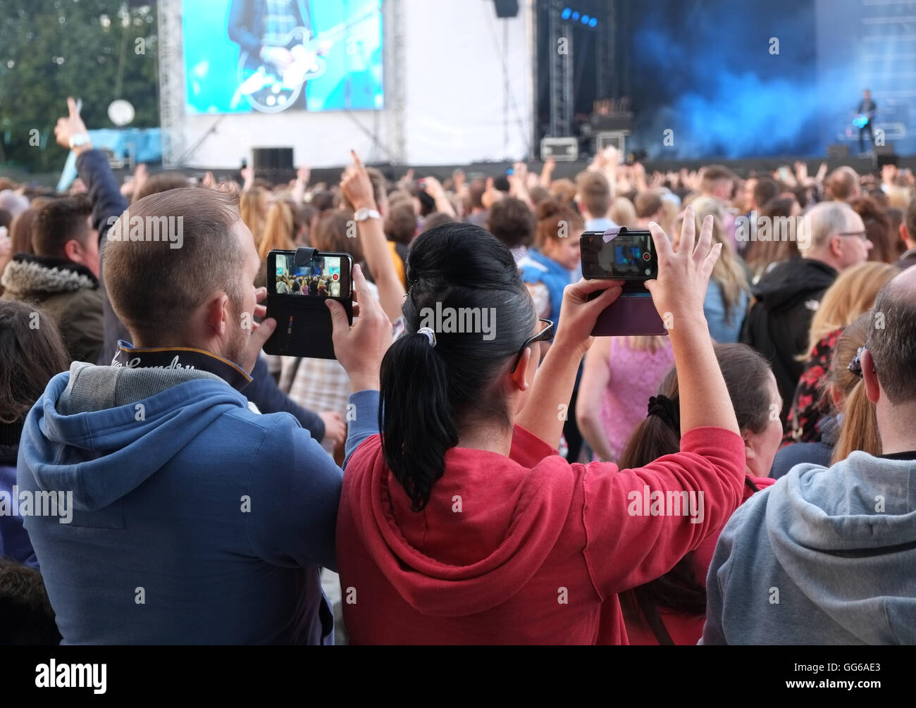 Couple make video on their phones, Tennents Vital, Boucher Road, Belfast,audience, - Stock Image