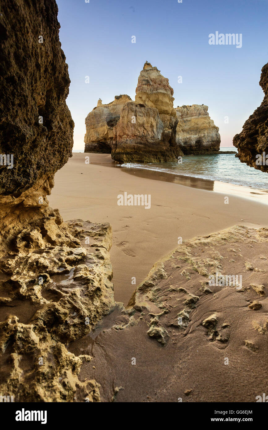 A sea cave frames the ocean and the imposing cliffs at dawn, Praia da Rocha, Portimao, Faro district, Algarve, Portugal, - Stock Image