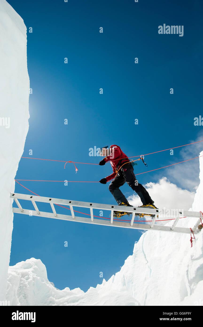 A climber makes his way across a crevasse using a temporary ladder, Khumbu region, Himalayas, Nepal, Asia - Stock Image