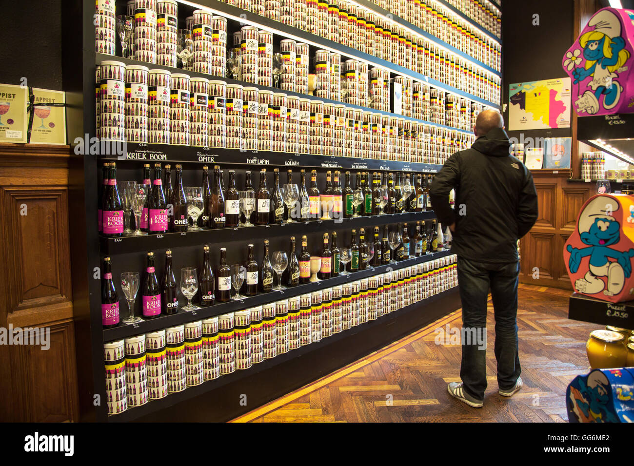 Tourist looking at collection of Belgian beers for sale in souvenir shop in Belgium - Stock Image