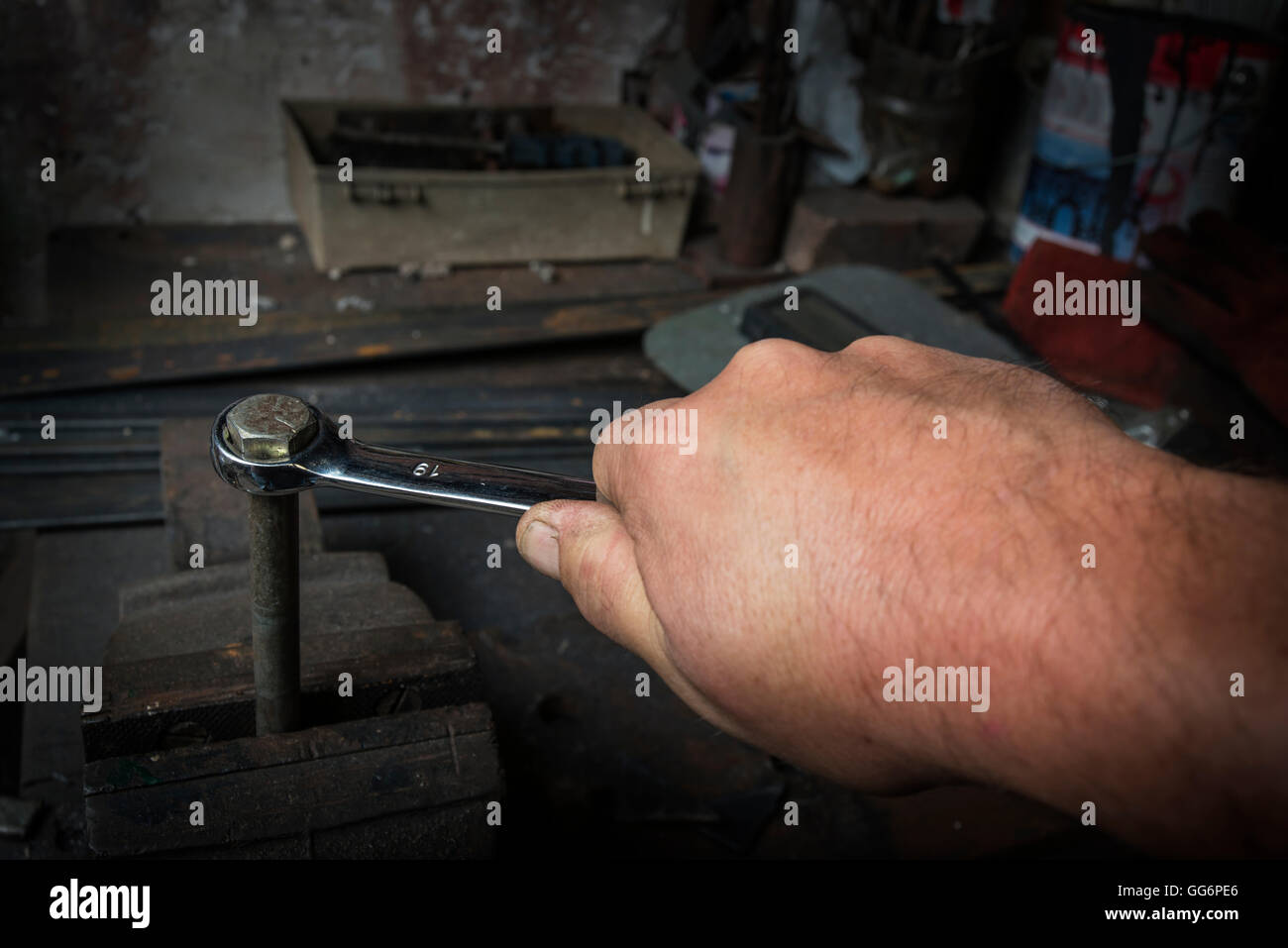 worker hand tightening or loosening a nut of a rusty bolt with a wrench in old workshop - Stock Image