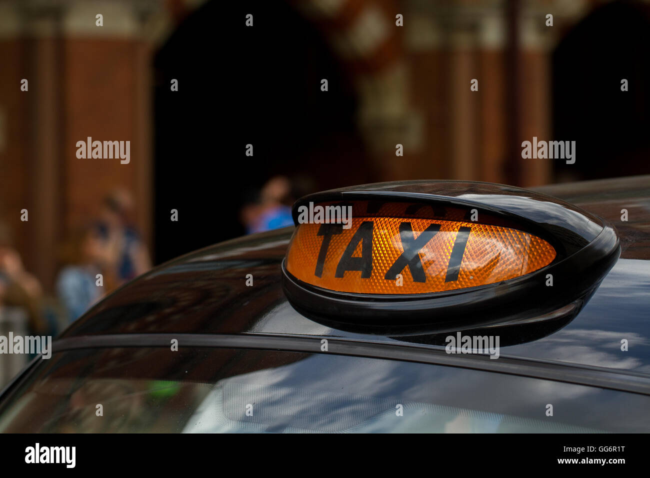 The illuminated orange Taxi sign on the roof of a London black cab with city streets in the background. - Stock Image