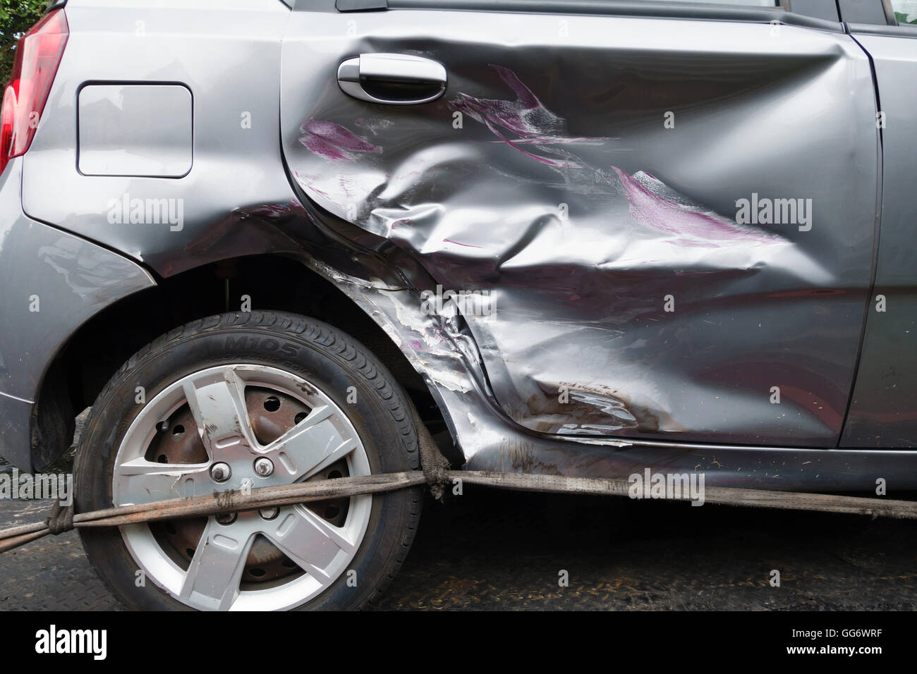 UK. A car with a badly dented rear door following a collision with another vehicle - Stock Image