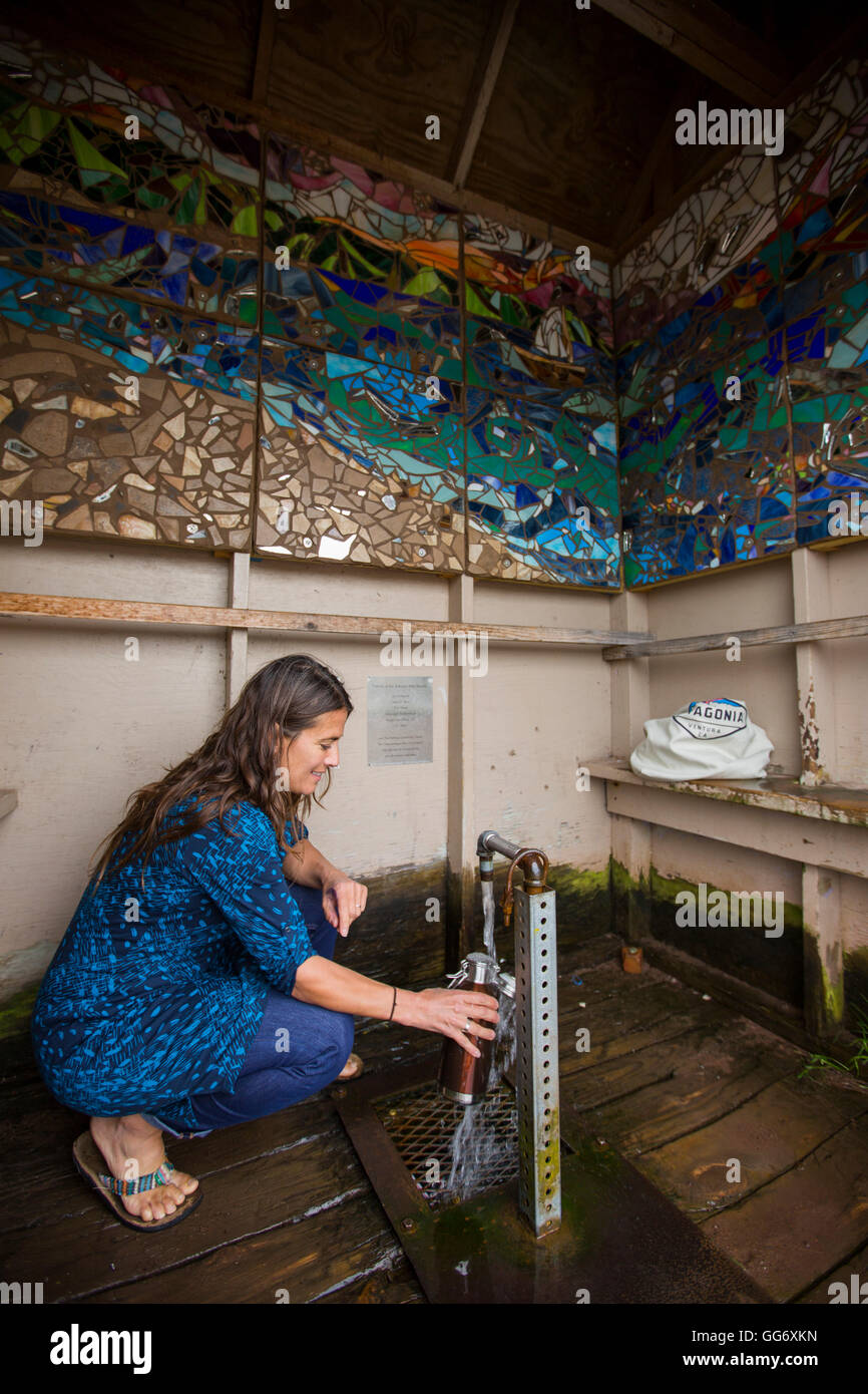 An adult woman fills up a resusable water bottle at an artesian well. - Stock Image