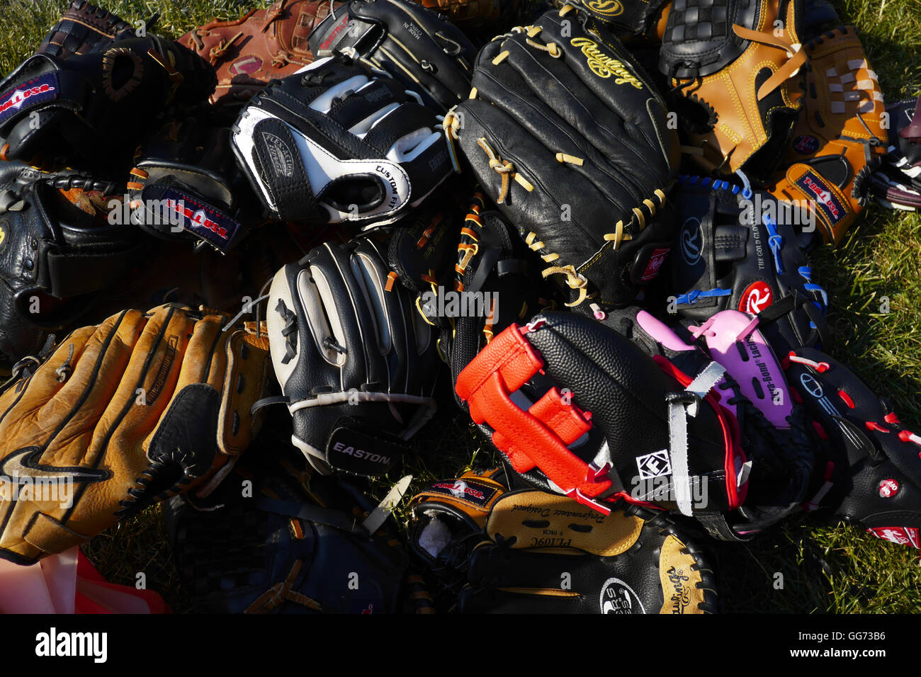 Piles of well-used baseball mitts for kids and adults piled on grass in the sun. - Stock Image