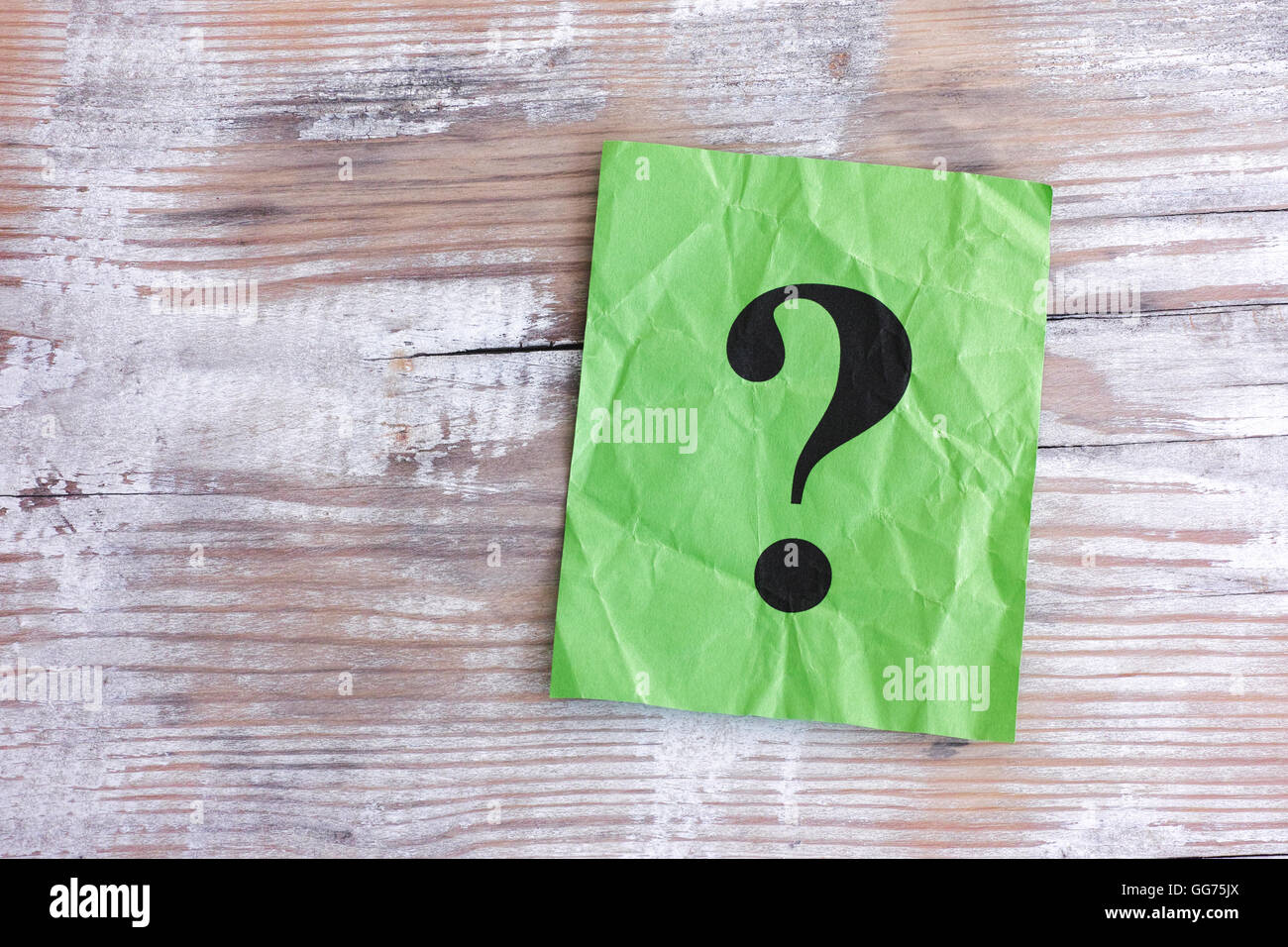 Green paper note with question mark on wooden background. Close up. - Stock Image