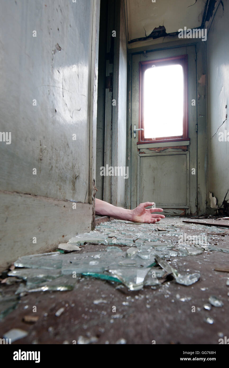 A person lying in doorway unconscious in messy environment. - Stock Image
