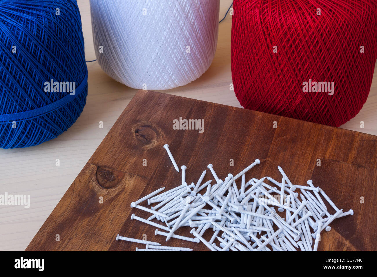 White Craft Nails And Other Accessories For String Art On A Wooden