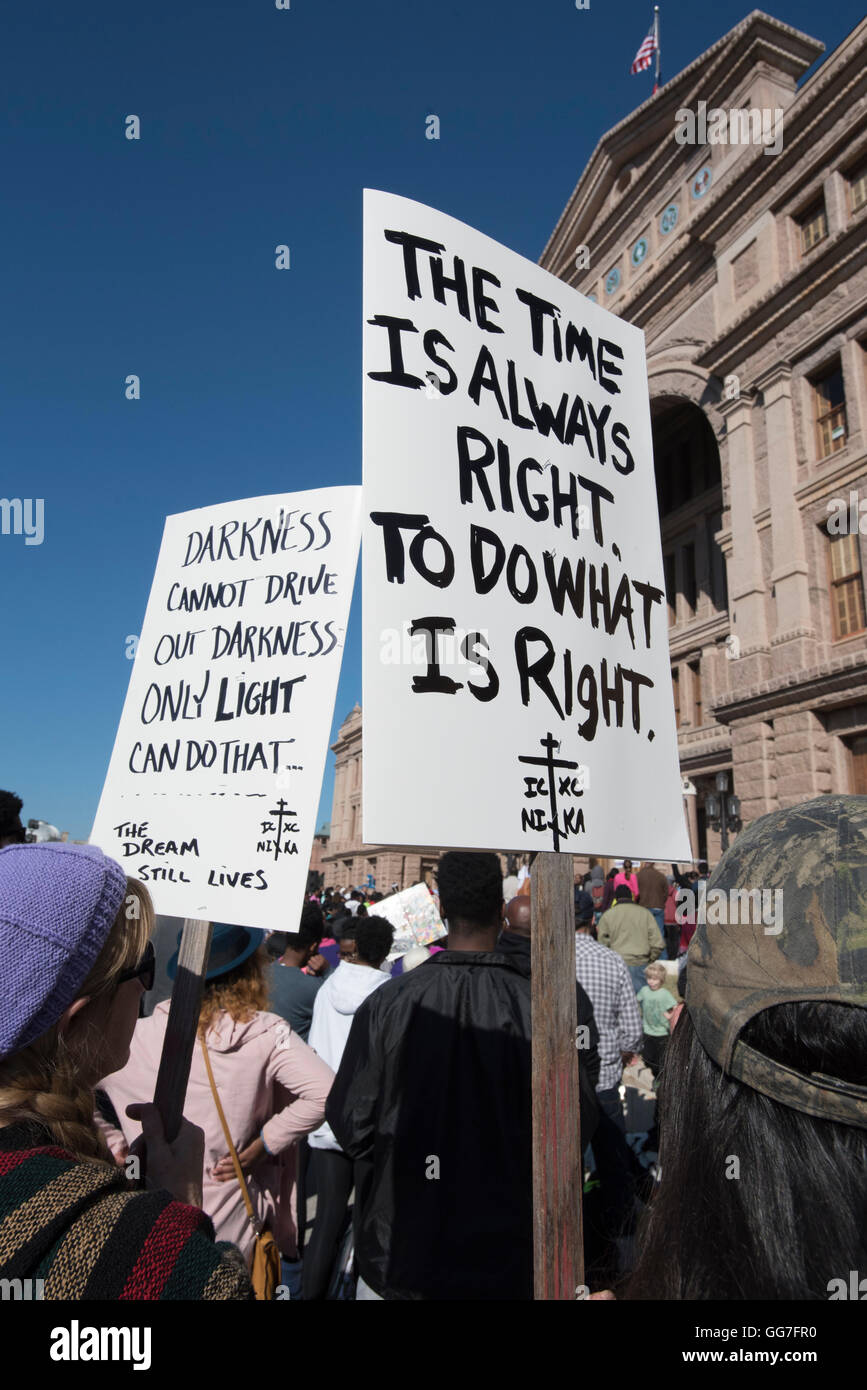 Marcher holds placard with Martin Luther King quote during MLK Day rally at the state Capitol building in Austin. - Stock Image