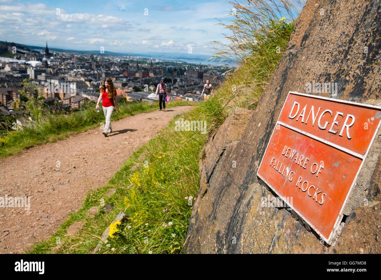 Walkers on Radical road footpath beneath Salisbury Crags high above Edinburgh in Scotland, United Kingdom - Stock Image