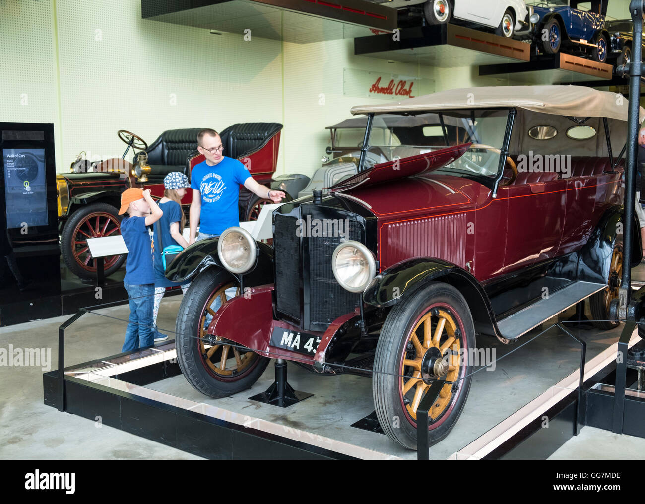 Visitors looking at vintage car on display at Riverside Museum of transport in Glasgow, Scotland, United Kingdom - Stock Image