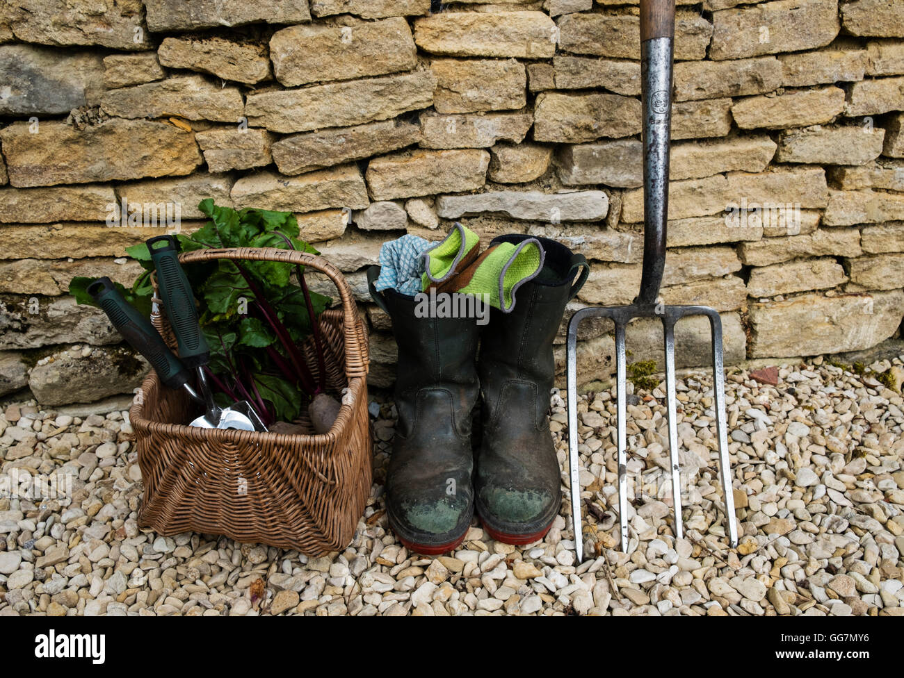 Detail of gardeners tools and boots in an English garden - Stock Image