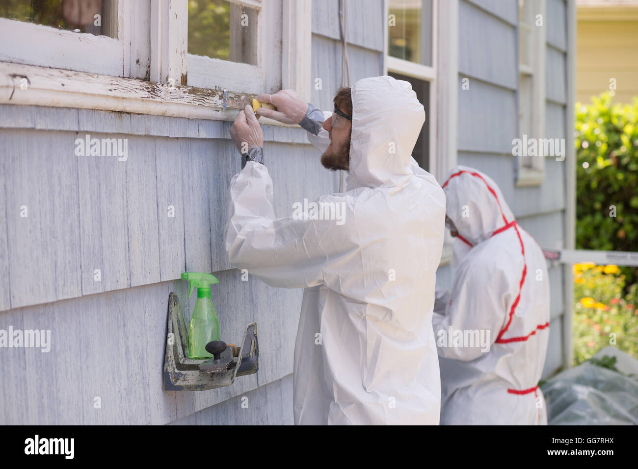 Two house painters in hazmat suits removing lead paint from an old house. - Stock Image