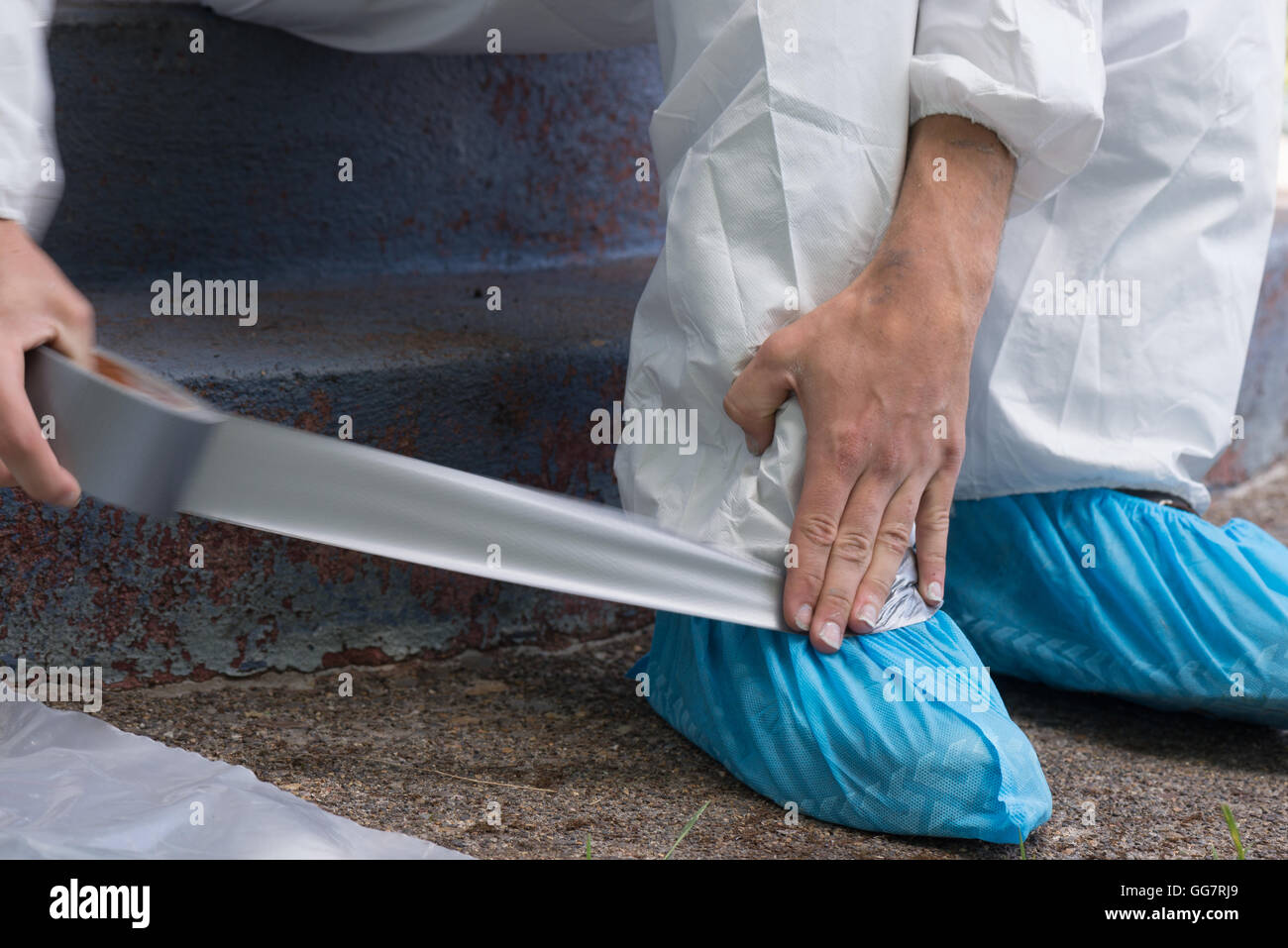 A house painter secures the ankles of his hazmat suit preparing to safely remove lead paint. - Stock Image