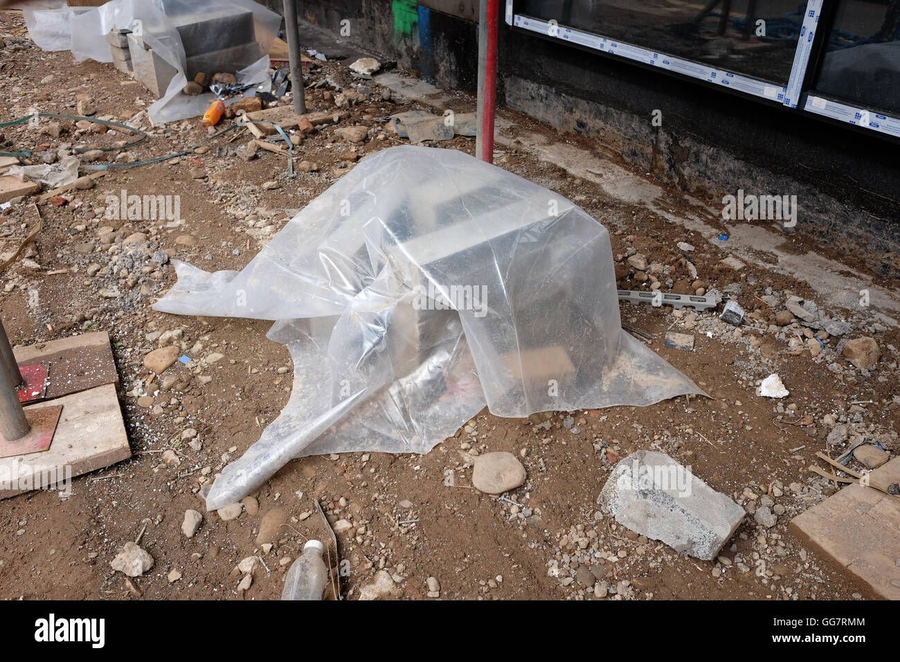 Stack of new blockwork protected from the rain with polythene sheeting. 3rd August 2016 - Stock Image
