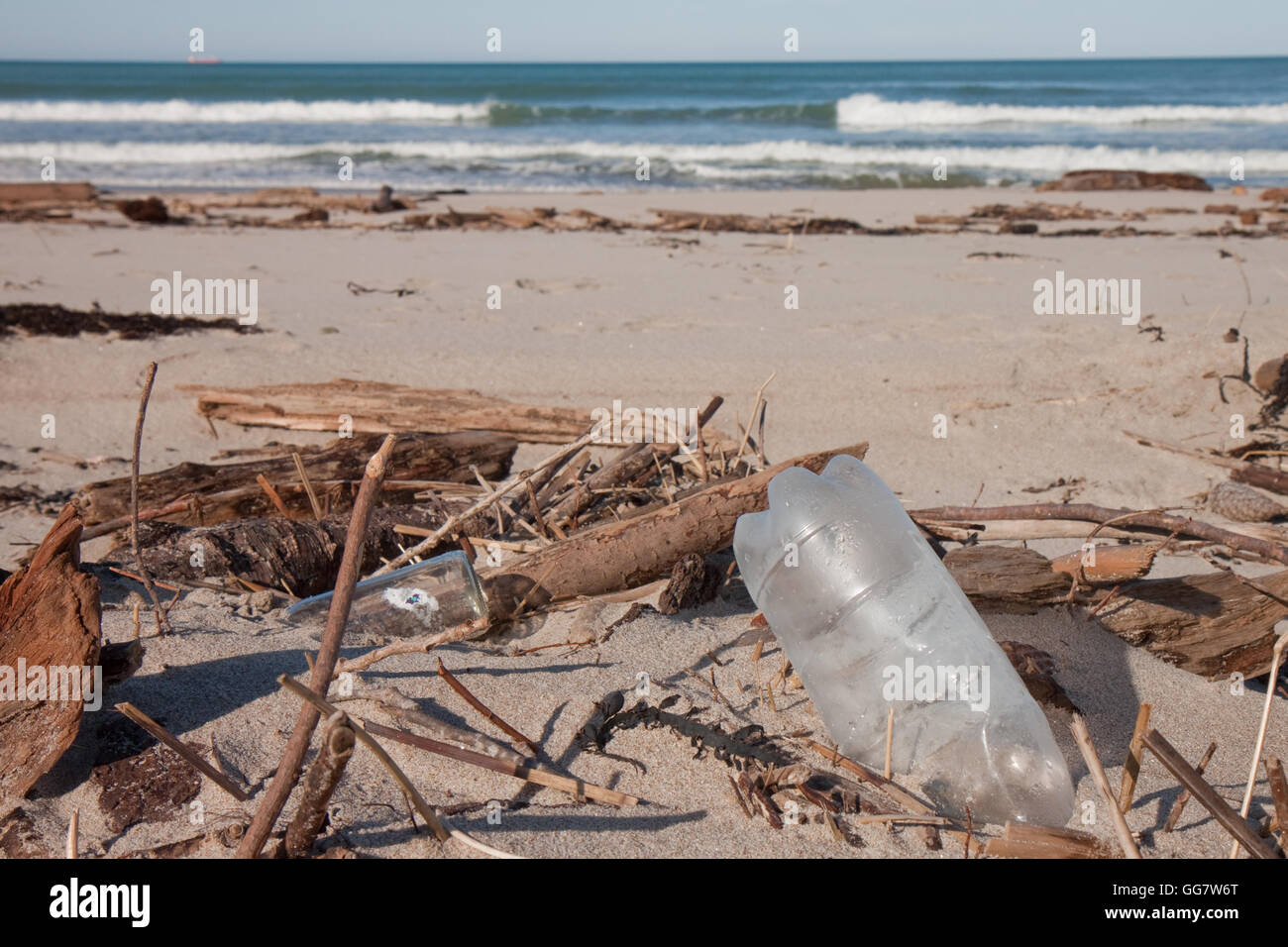bottles and other plastic littered on a beach in Gisborne, New Zealand - Stock Image