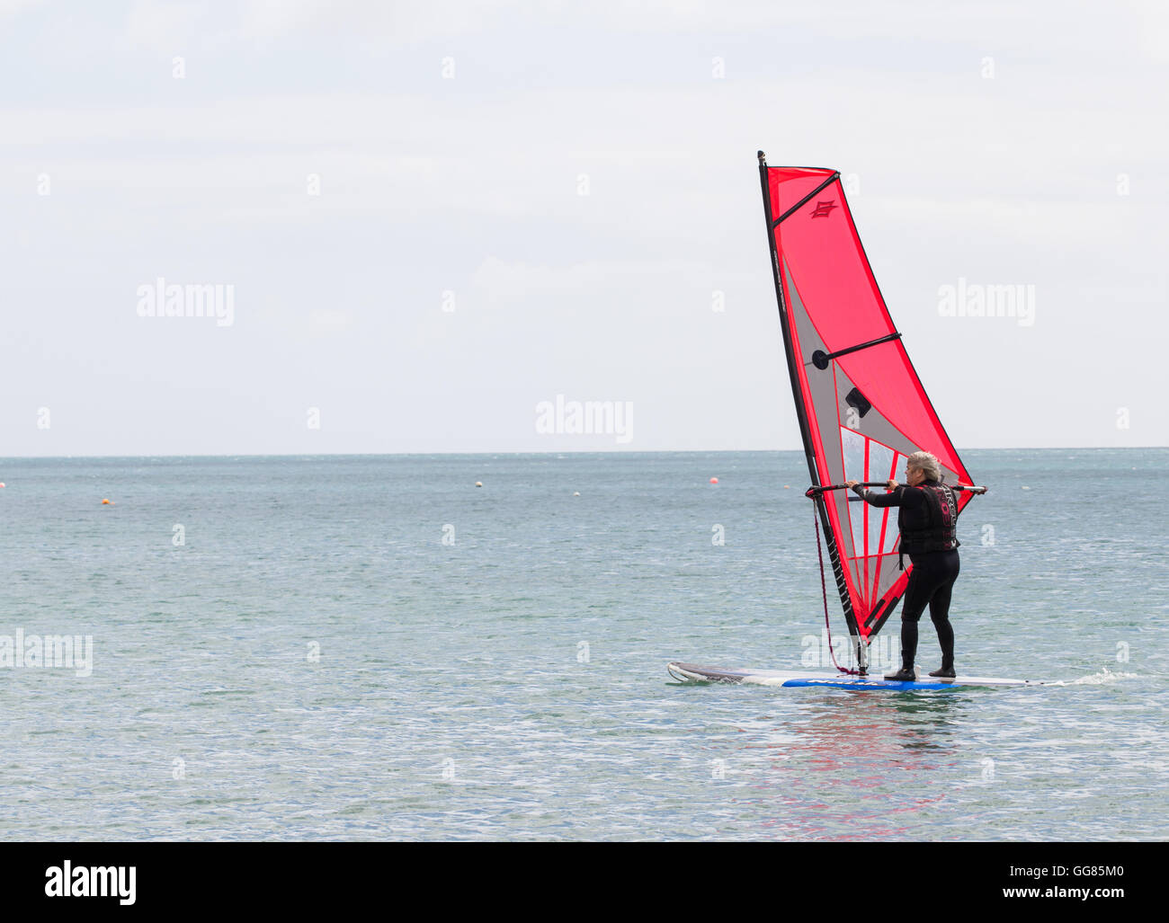 An elderly man in a wet suit keeping active and enjoying a windsurfing lesson on a calm, flat ocean. - Stock Image