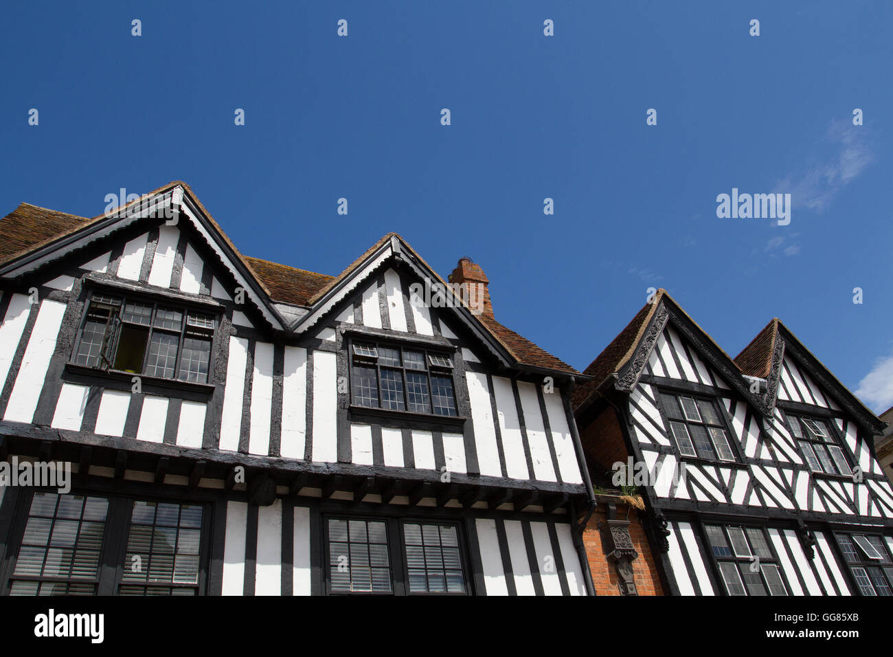A row of Tudor style houses in England with traditional black and white facades under a clear, blue sky. - Stock Image