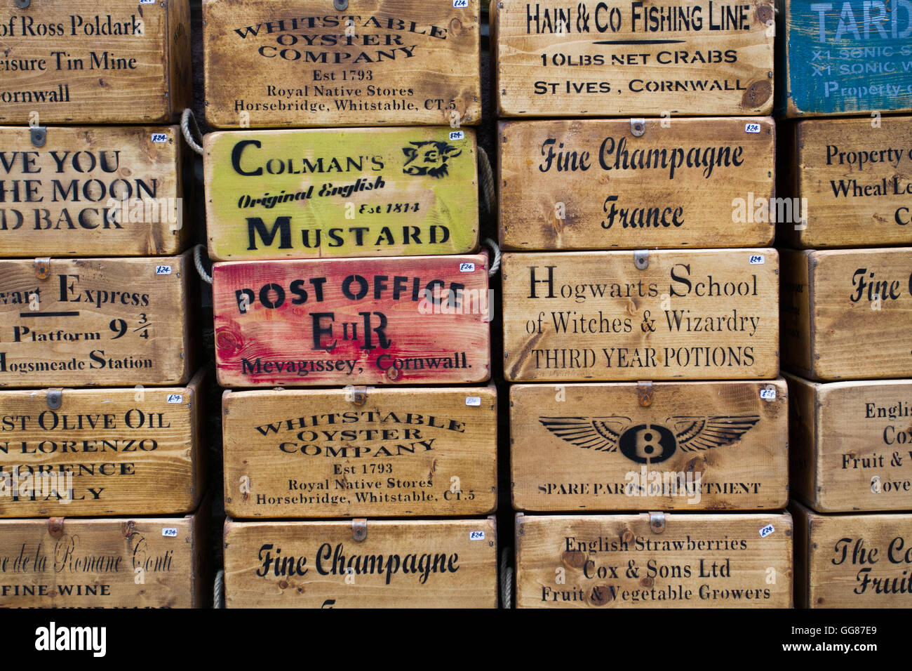 Antique and old wooden boxes stacked up on top of each other with adverts,commercials and printed messages on the - Stock Image